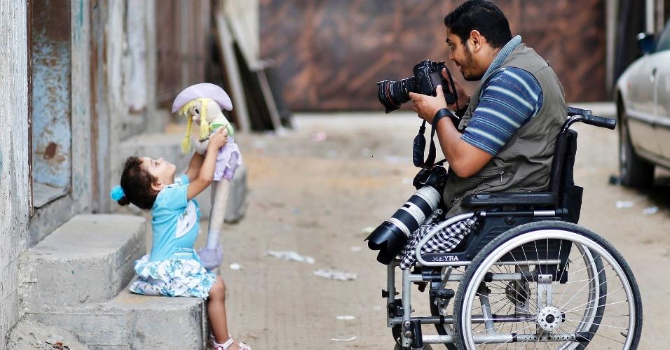 1º.out.2012 - Moamen Qreiqea, cadeirante e fotógrafo, tira fotos de sua filha em frente à sua casa em Gaza. Qreiqea perdeu suas duas pernas após ataque aéreo israelense em 2008, enquanto tirava fotos em Gaza