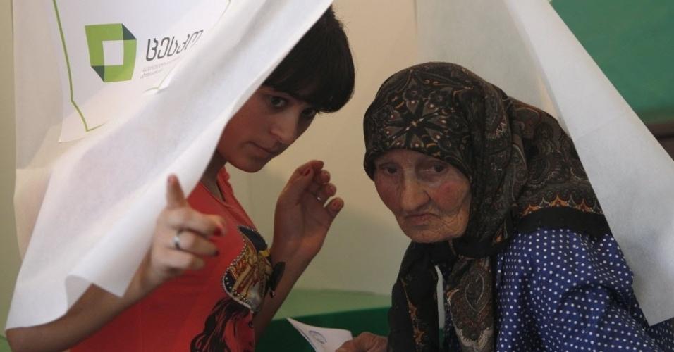 1º.out.2012 - Mulher deixa cabine de votação em um vilarejo próximo a Tbilisi, na Geórgia, em dia de eleições parlamentares nacionais.