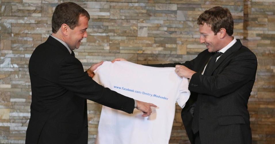 1º.out.2012 - O primeiro-ministro russo, Dmitri Medvedev (esq.), recebe nesta segunda-feira (1º), uma camiseta com o link para a página do seu Facebook na internet, das mãos do CEO do site, o norte-americano Mark Zuckerberg, durante encontro no palácio de Gorki, perto de Moscou, na Rússia
