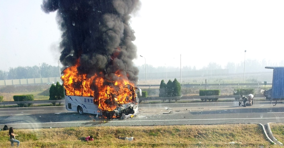 1º.out.2012 - Ônibus turístico pega fogo após se chocar com caminhão em estrada de Tianjin, na China. De acordo com a imprensa local, o acidente deixou seis mortos, incluindo cinco alemães, e deixou ao menos 14 pessoas feridas