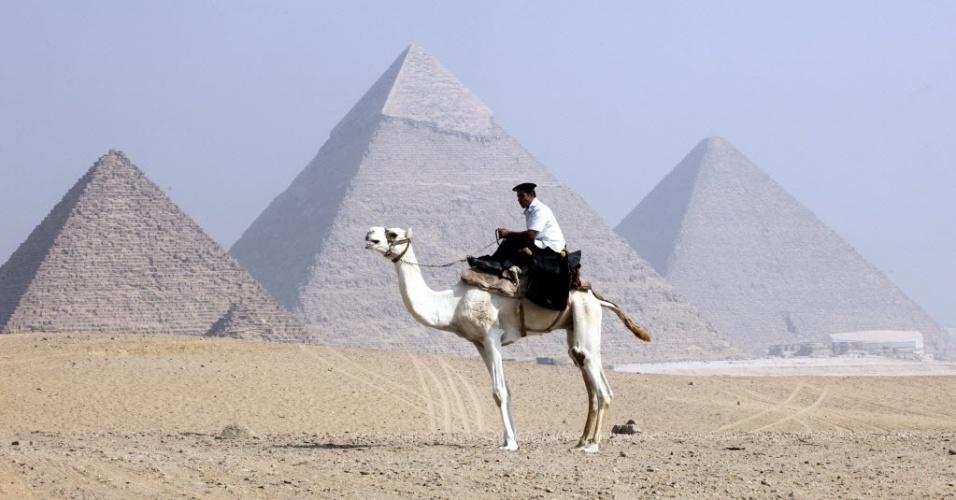 1º.out.2012 - Policial faz patrulha sobre um camelo em frente às pirâmides de Giza no primeiro dia do Rali dos Faraós, nas cercanias de Cairo, no Egito