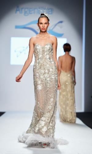 Desfile de Gabriel Lage na semana de moda de Milão Primavera/Verão 2013. Vestido tomara que caia prateado leva aplicações de flores de tecido e canutilhos. Detalhe para as plumas da barra (19/09/2012)