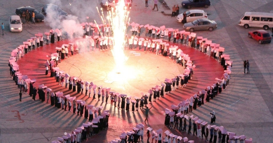 2.set.2012 - Moradores de Benghazi e ativistas formam uma corrente humana em forma de uma fita rosa durante evento de conscientização a respeito do câncer de mama na Líbia