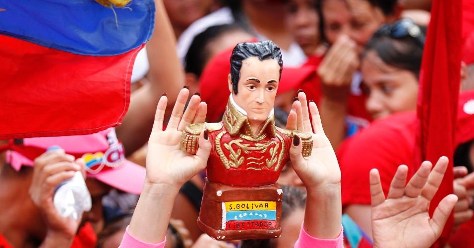 3.out.2012 - Apoiador do presidente e candidato à reeleição na Venezuela, Hugo Chávez, mostra uma estátua de Simon Bolívar durante comício. Bolívar foi comandante das tropas independentistas em parte da América do Sul e acreditava que o melhor para a região era a não divisão em países menores, como ocorreu após a independência. Chávez usa a imagem de Bolívar como líder venezuelano
