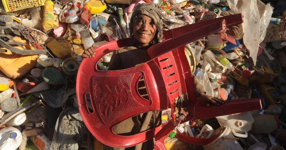 3.out.2012 - Garoto de 13 anos encaixa a cabeça em furo de cadeira em meio a uma pilha de coisas descartadas no Afeganistão. Ele ganha o equivalente a R$ 0,60 por quilo de plástico vendido. De acordo com o Banco Mundial, mais de um terço da população do país vive abaixo da linha de pobreza