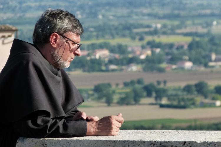 Homem religioso observa paisagem de Assis, cidade de São Francisco e destino de devotos do mundo inteiro