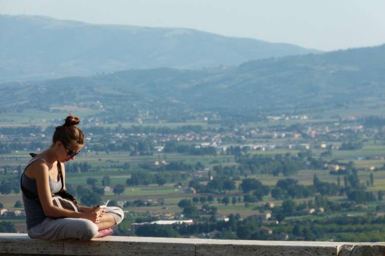 Turista lê livro em mirante da cidade italiana de Assis, terra de São Francisco