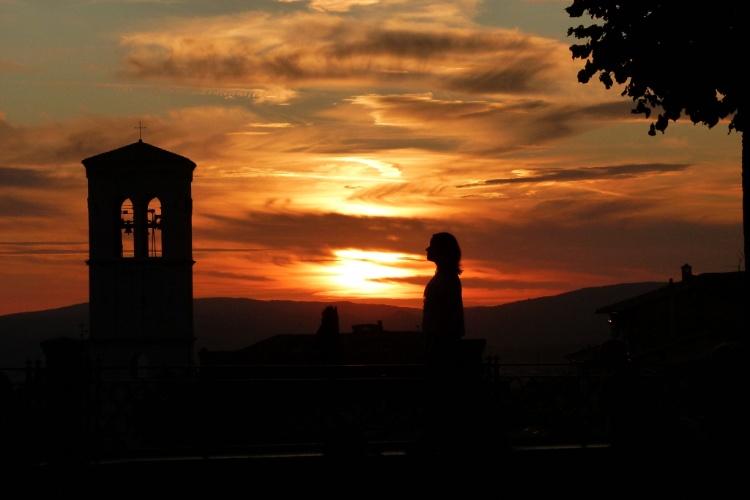 Turista observa o pôr do sol desde mirante da cidade de Assis, um dos destinos mais sagrados da Itália