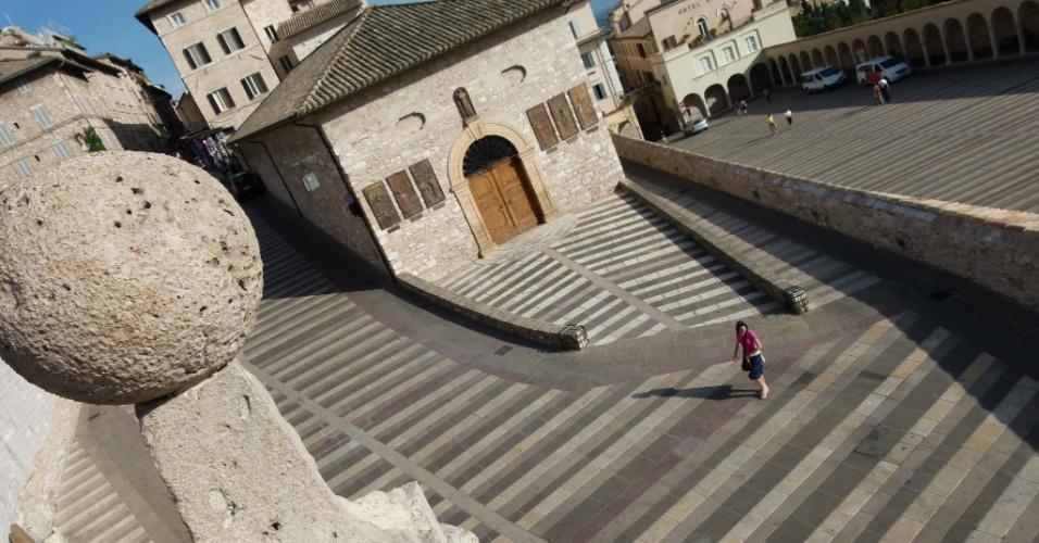Viajante caminha pelo centro histórico de Assis, uma das cidades mais sagradas da Itália