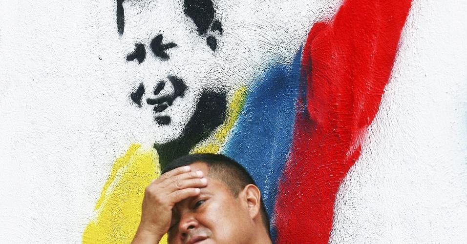 5.out.2012 - Homem diante de grafite representando o presidente e candidato Hugo Chávez, em Caracas. As eleições presidenciais venezuelanas acontecem neste domingo (7)