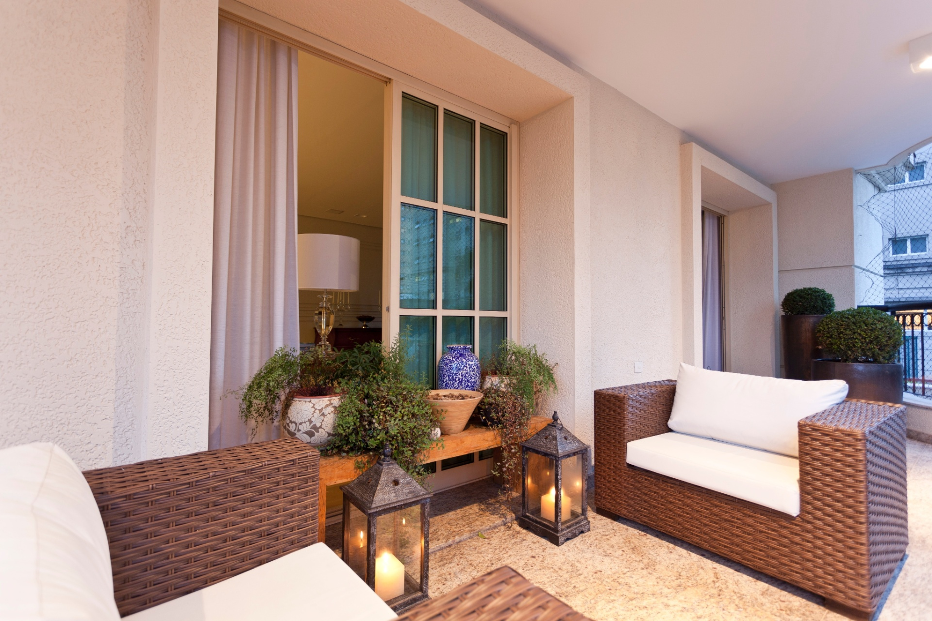 Na varanda, cercada de floreiras, o granito do piso não é polido, para preservar seu aspecto mais rústico e natural, propício para áreas externas. A decoração se perfaz em móveis de palha sintética e objetos de decoração para jardim - todos L'Oeil
