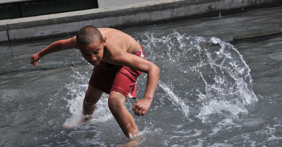 6.out.2012 - Menino se banha em espelho d'água do Masp (Museu de Arte de São Paulo), na Avenida Paulista, em São Paulo. A temperatura na capital nesta tarde é de 29°C