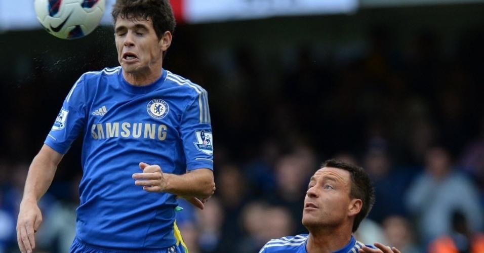 Oscar tenta o cabeceio enquanto é observado por Terry na partida do Chelsea contra o Norwich, pelo Campeonato Inglês