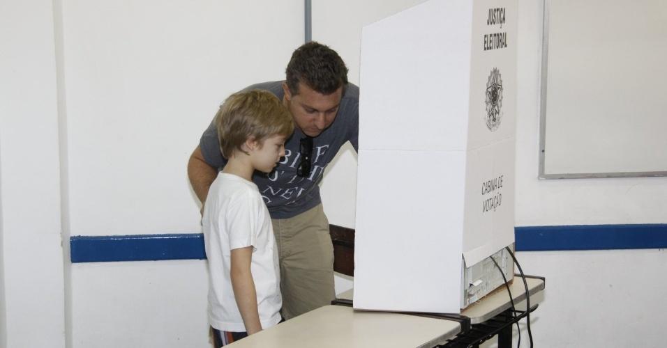 O apresentador Luciano Huck mostra ao filho Joaquim como votar