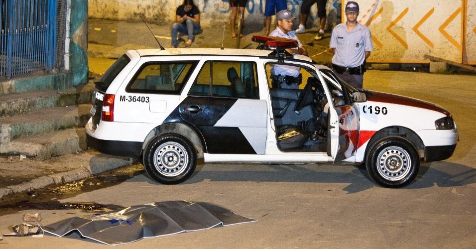 9.out.2012 - Policiais observam corpo de homem morto a tiros em Taboão da Serra (SP)