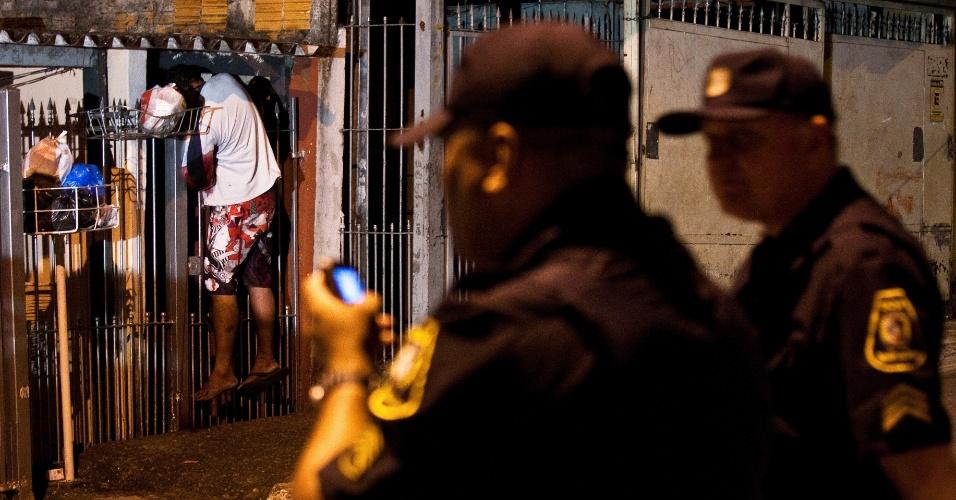 9.out.2012 - Policiais observam homem morto durante onda de mortes que ocorreu na madrugada desta terça-feira (9) em Taboão da Serra e Embu das Artes, na Grande São Paulo