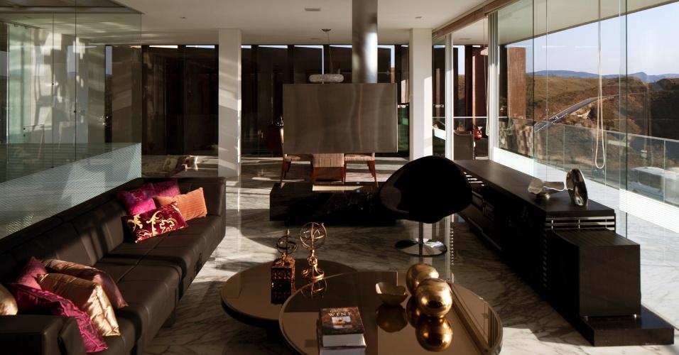 Móveis escuros dão o tom da sala de estar da casa NB; à direita, portas de vidro - do chão ao teto - dão acesso à varanda que percorre toda a fachada principal da residência. A construção, em Nova Lima (MG), tem projeto de Alexandre Brasil e Paula Zasnicoff, do escritório Arquitetos Associados