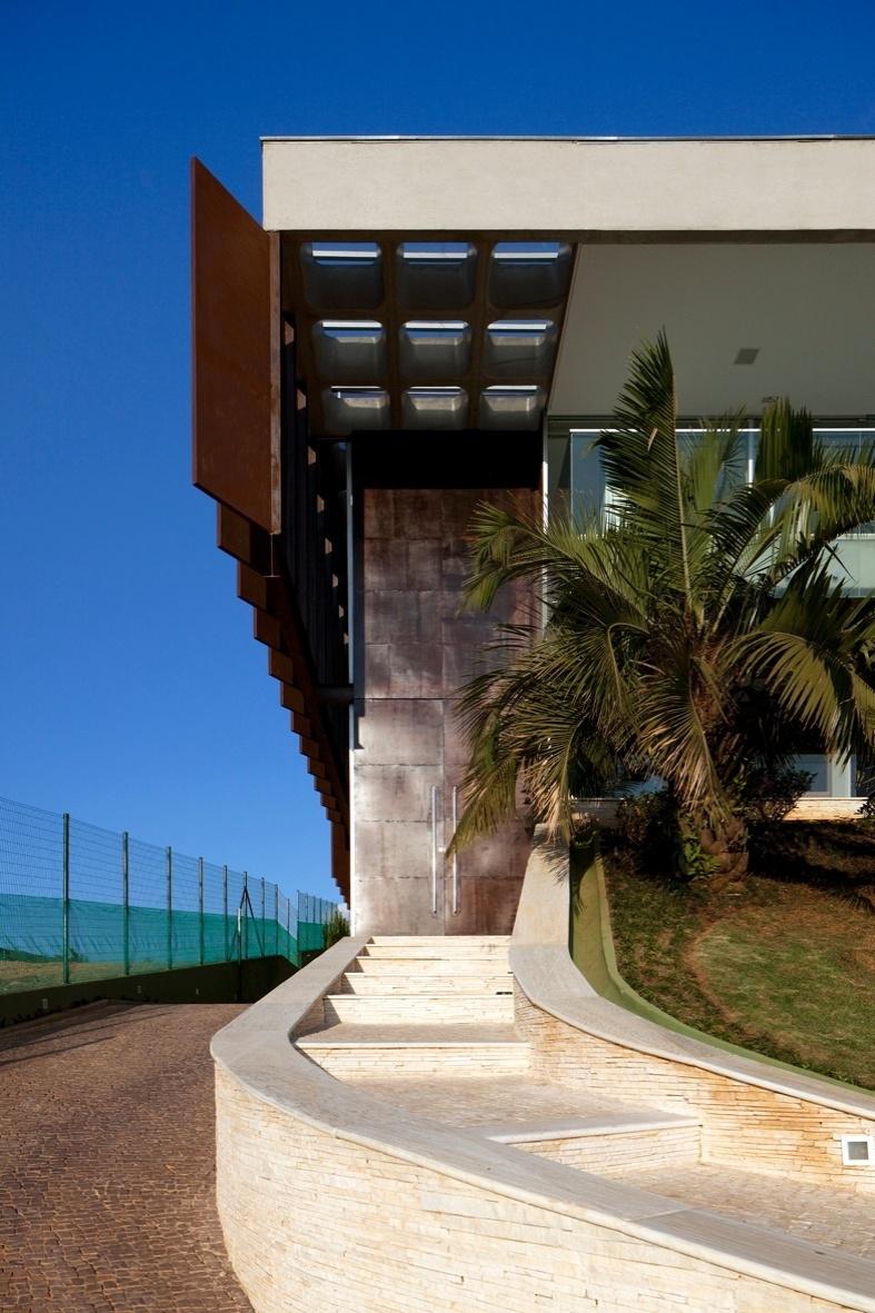 A entrada social da casa NB, em Nova Lima (MG), se faz por uma grande porta de metal. A construção foi implantada na parte mais alta do terreno em declive, com 1.300 m². O projeto é dos Arquitetos Associados, de Belo Horizonte