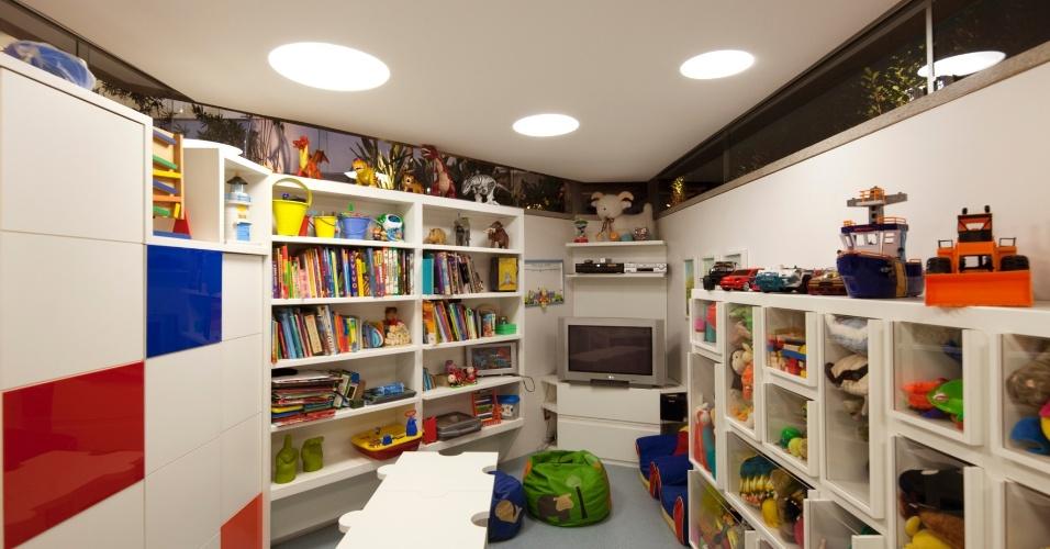 Sob a sala íntima, na área de circulação, está a brinquedoteca no piso inferior - semi-enterrada. O espaço repleto de estantes, conta com pufes e uma mesa com banquinhos. As janelas junto ao forro se alinham com um jardim rebaixado em relação ao deck da piscina, no pátio de lazer. A casa NB, em Nova Lima (MG), tem projeto de Alexandre Brasil e Paula Zasnicoff, do escritório Arquitetos Associados