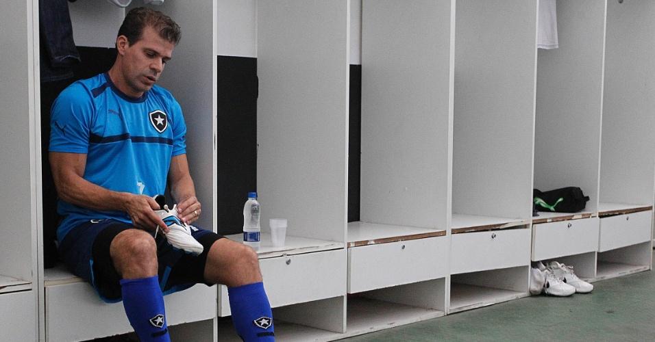 Túlio calça chuteiras antes de entrar em campo para treinamento pelo Botafogo