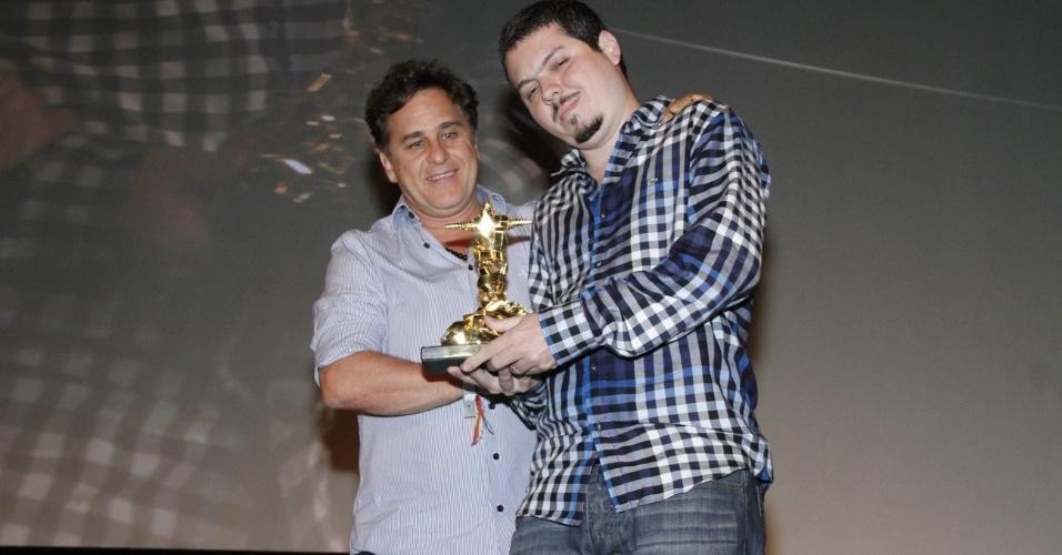 """O diretor de """"Éden"""", Bruno Safadi (à dir.), recebe das mãos de Marcos Frota o prêmio de melhor atriz que seria entregue a Leandra Leal. A atriz não foi à cerimônia porque está de férias (11/10/12)"""