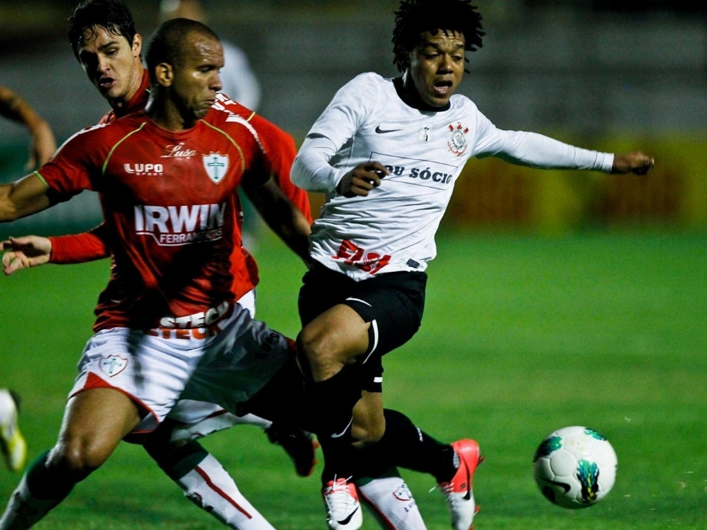 Romarinho sofre marcação de dois jogadores da Portuguesa no duelo no Canindé