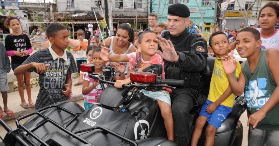 14.out.2012 - Após ocupação das favelas do Complexo de Manguinhos, na zona norte do Rio de Janeiro, crianças da comunidade interagem com policiais