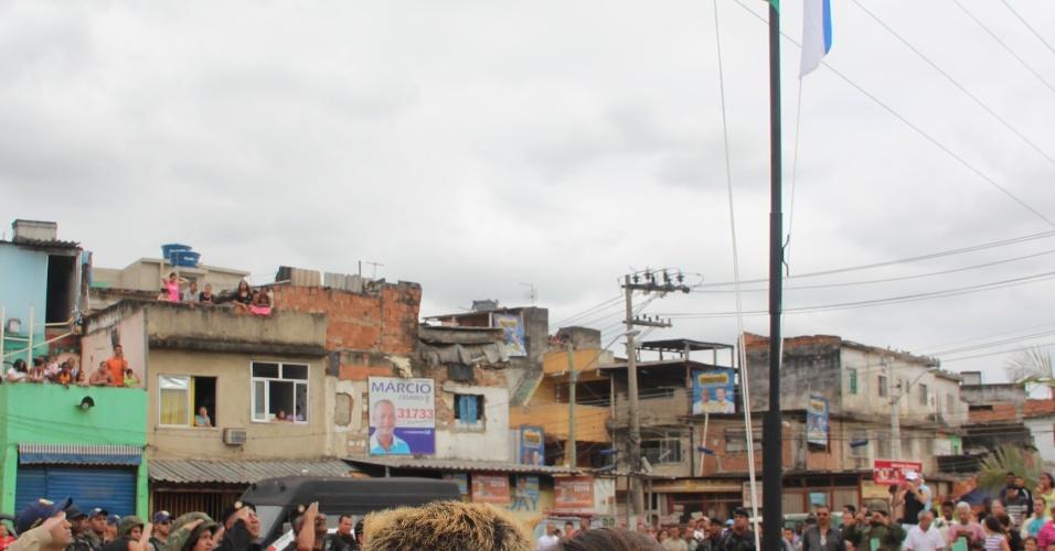 14.out.2012 - Após ocupação das favelas do Complexo de Manguinhos, na zona norte do Rio, policiais hasteiam bandeiras do Brasil e do Estado em uma praça da comunidade