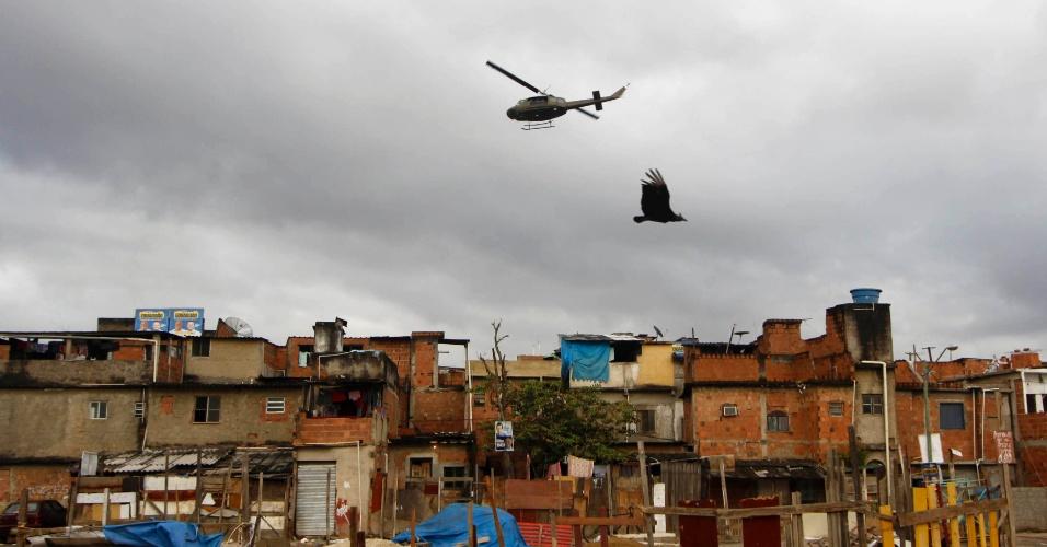 14.out.2012 - Helicóptero da Polícia Militar sobrevoa as favelas do Complexo de Manguinhos, na zona norte do Rio de Janeiro, durante o processo de ocupação da comunidade para dar início a instalação de UPPs (Unidades de Polícia Pacificadora)