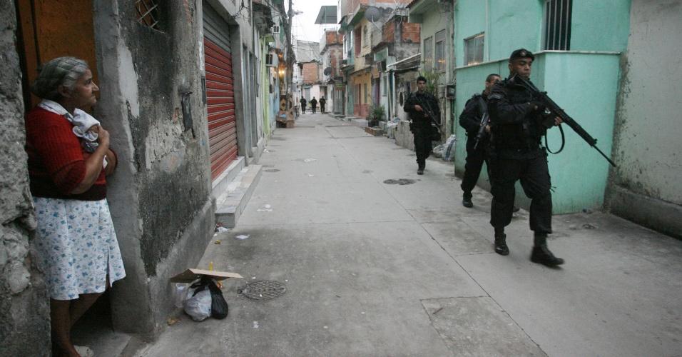 14.out.2012 - Moradora observa policiais do Bope (Batalhões de Operações Policiais Especiais) fazerem vistoria pelas ruas das favelas do Complexo de Manguinhos, na zona norte do Rio de Janeiro, durante o processo de ocupação da comunidade para dar início a instalação de UPPs (Unidades de Polícia Pacificadora)