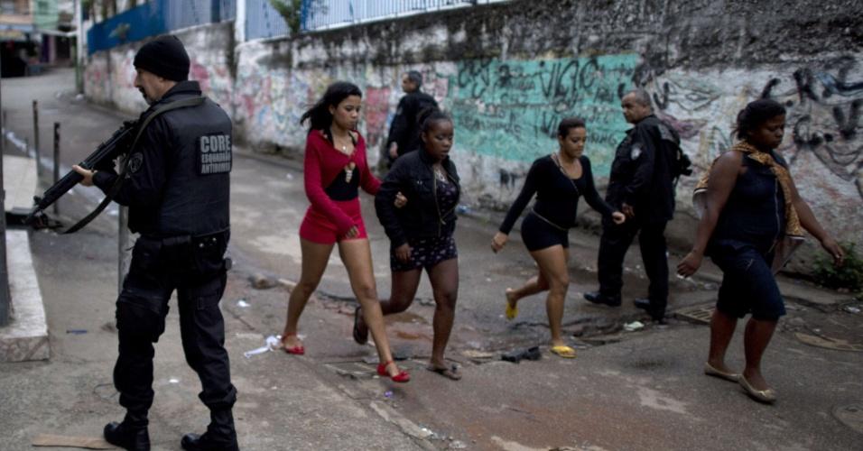 14.out.2012 - Moradores caminham em meio a policiais durante processo de ocupação nas favelas do Complexo de Manguinhos, na zona norte do Rio de Janeiro