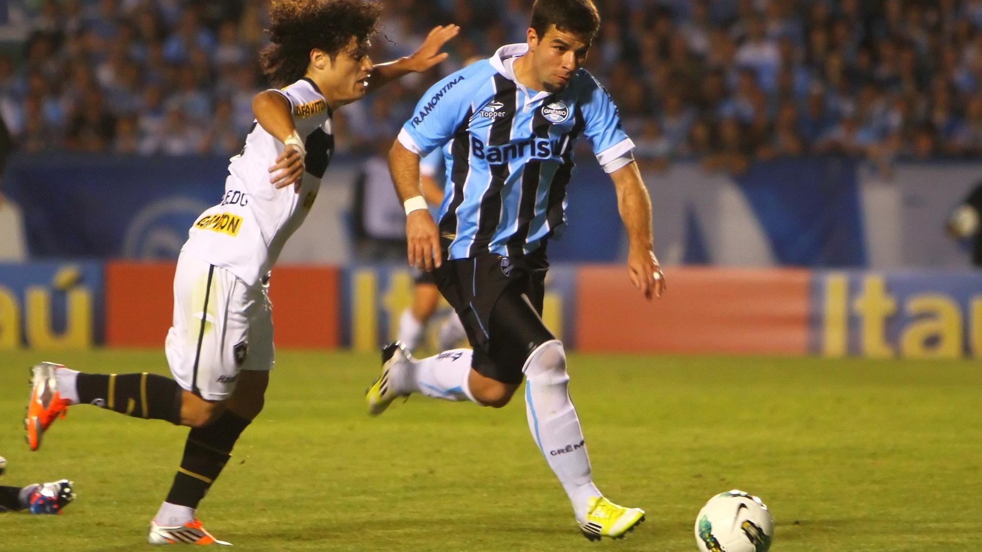 André Lima, do Grêmio, carrega a bola com a marcação de Márcio Azevedo, do Botafogo