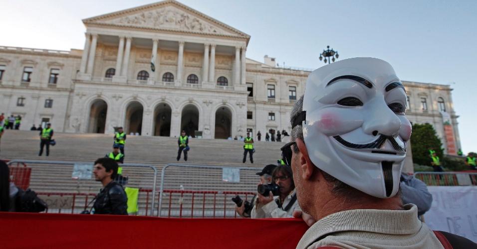 15.out.2012 - Homem com máscara de Guy Fawkes protesta em frente ao Parlamento português em Lisboa, em Portugal. O primeiro-ministro português, Pedro Passos Coelho, prometeu continuar aplicando as medidas de austeridade no país