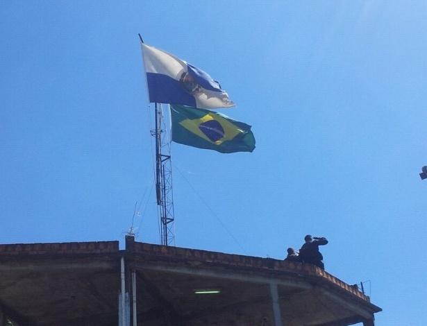 16.out.2012 - Policiais do Bope batem continência diante das bandeiras do Brasil e do Estado do Rio de Janeiro, no alto da favela do Jacarezinho, no Rio