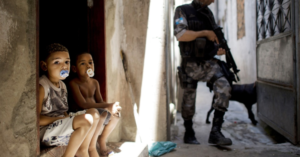 16.out.2012 - Policial procura por drogas, auxiliado por um cão farejador, na favela do Jacarezinho, observado por garotos