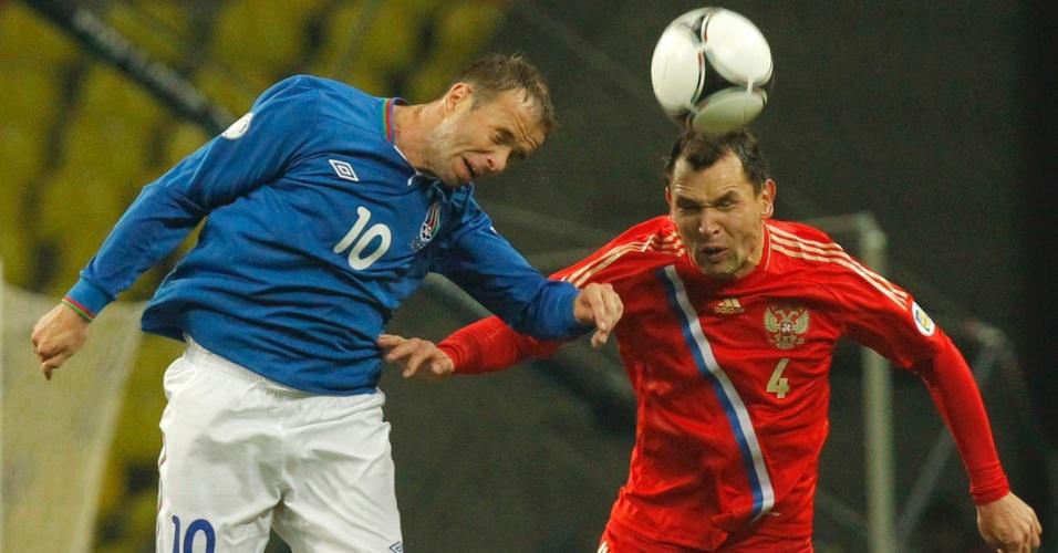 16.out.2012 - Ignashevich, da Rússia, e Subasic, do Azerbaijão, disputam bola de cabeça em Moscou; russos ganharam por 1 a 0
