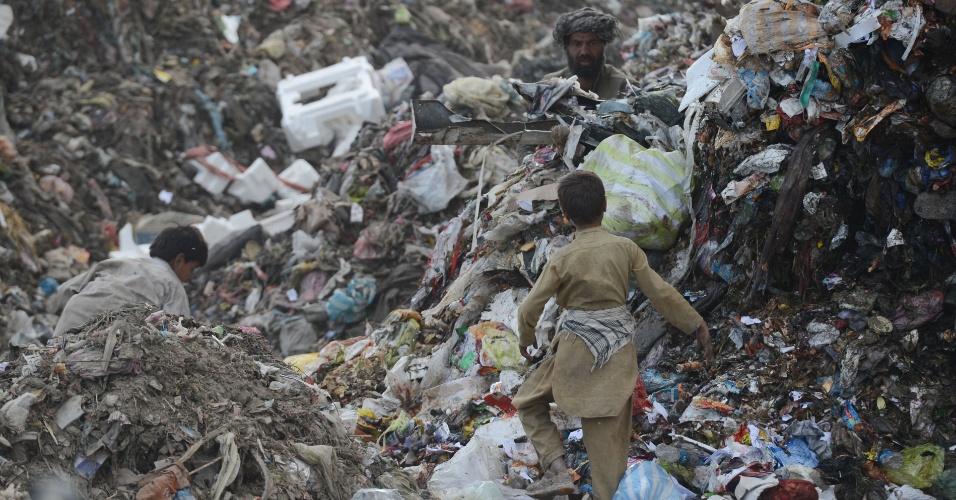 17.10.2012 - Crianças afegãs procuram material reciclável em lixão localizado no subúrbio de Cabul, no Afeganistão
