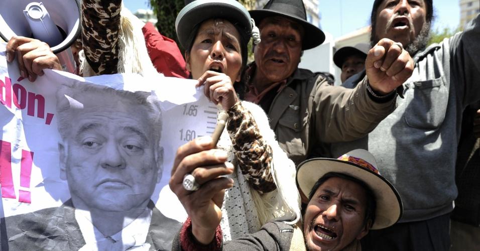 17.10.2012 - Moradores da cidade boliviana de El Alto protestam em frente à embaixada dos Estados Unidos em La Paz, na Bolívia, nesta quarta-feira (17). Os manifestantes pedem a extradição do ex-presidente Gonzalo Sanchez de Lozada - cuja imagem aparece no pôster da foto. Lozada, que governou a Bolívia em dois períodos, de 1993 a 1997 e de 2002 a 2003, está exilado nos EUA desde 2003. Ele renunciou à presidência e saiu da Bolívia em meio a um levante popular que deixou 65 mortos. O governo de La Paz deseja que o político seja julgado na Bolívia por crimes que teriam ocorrido em sua gestão