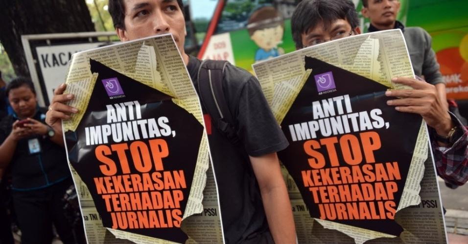 17.out.2012 - Jornalistas seguram cartazes com mensagens contra a violência contra jornalistas em frente à sede do Ministério da Defesa em Jacarta, na Indonésia