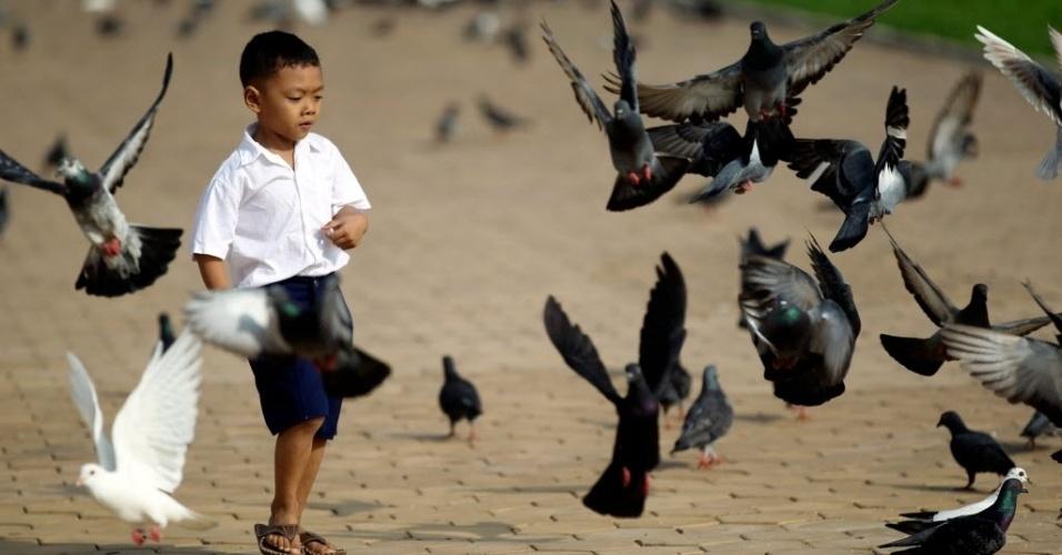 17.out.2012 - Menino caminha perto de pombas em frente ao Palácio Real em Phnom Pehn, no Camboja