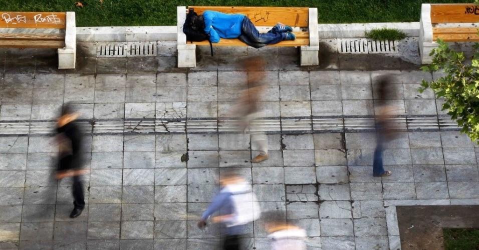 17.out.2012 - Pessoas caminham perto de sem-teto na Praça Syntagma, na área central de Atenas, na Grécia