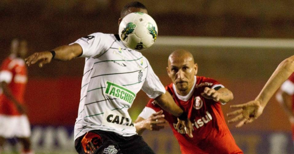 Jogador do Figueirense domina a bola observado de perto pelo volante Guinazu, do Internacional