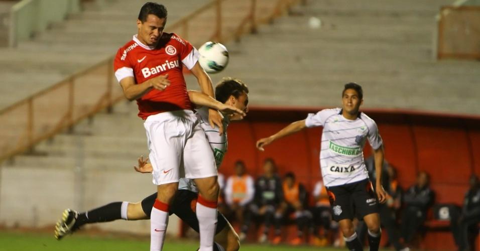 Leandro Damião sobe e cabeceia a bola cercado por dois jogadores do Figueirense, durante duelo no Beira Rio