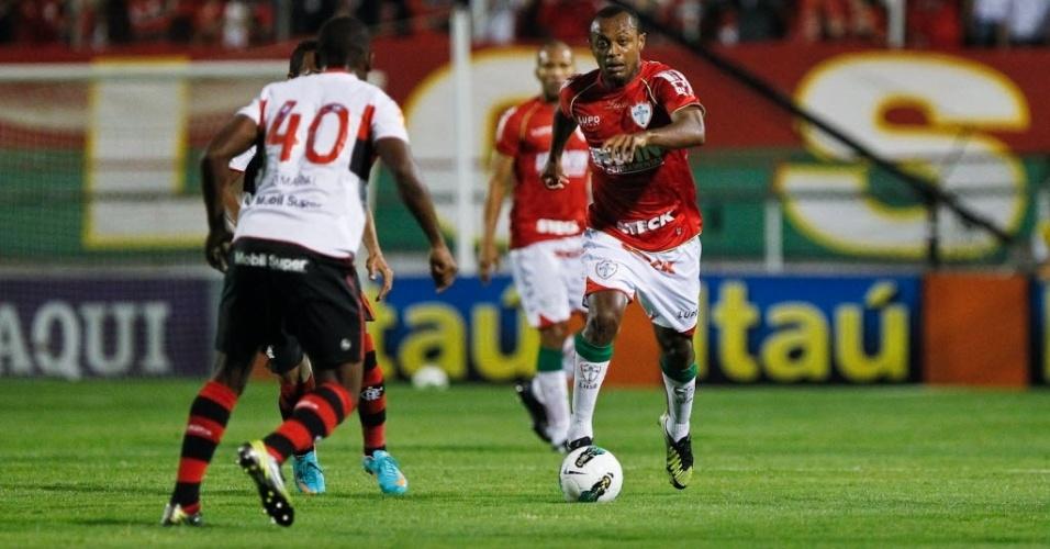 Léo Silva, volante da Portuguesa, conduz a bola observado por Amaral, do Flamengo, em jogo no Canindé
