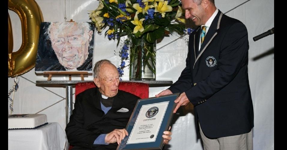 Padre Schneider (sobrenome não divulgado), professor mais velho em atividade, recebe certificado com seu recorde estabelecido de um representante do Guinness