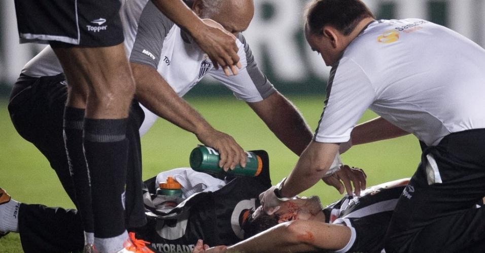 17.out.2012 - Rafael Marques, zagueiro do Atlético-MG, é atendido pelos médicos no gramado da Vila Belmiro após ficar desacordado no jogo contra o Santos