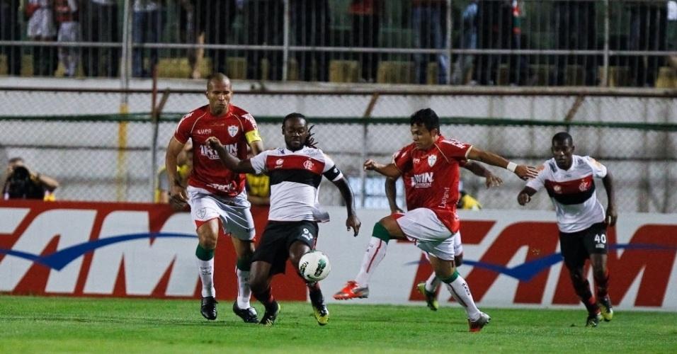 Vagner Love briga pela bola com dois jogadores da Portuguesa durante partida no Canindé, pela 31ª rodada do Brasileirão
