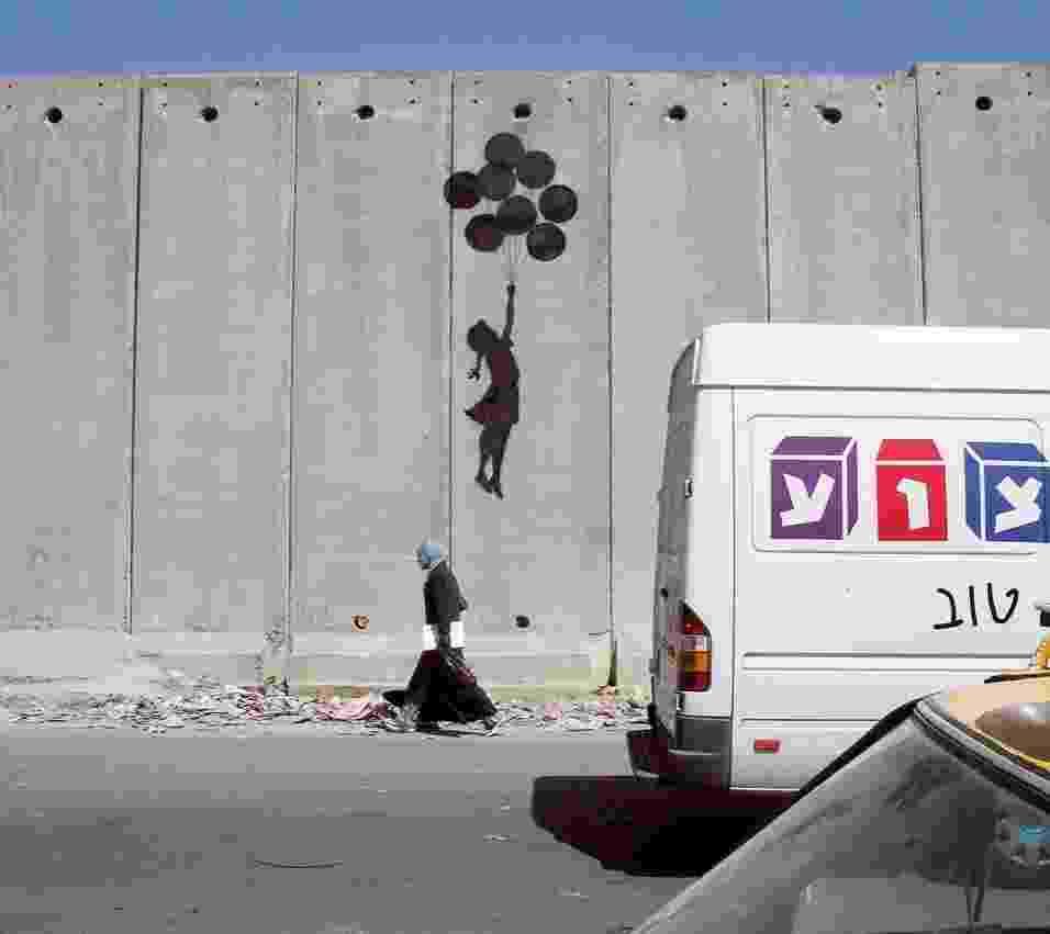"""Obra de Banksy pintada em muro de Belém, em 2005. O livro narra a conversa do artista com um idoso. O idoso pergunta: """"Você pintou o muro, ele ficou bonito"""". """"Obrigado"""", respondeu Banksy. """"Não queremos que esse muro fique bonito, nós odiamos esse muro, vá embora""""  - Divulgação"""