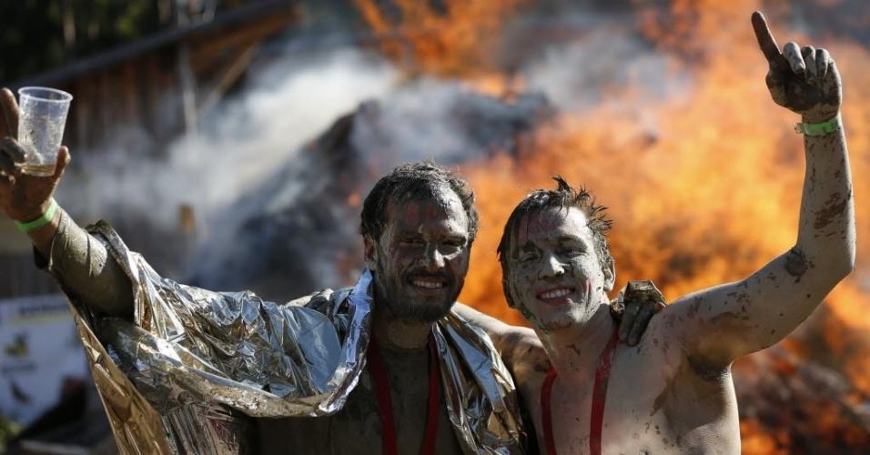 Austríacos comemoram em frente a um fogareiro após completarem a Wild Boar Dirt Run uma corrida de cross country com obstáculos e muita lama