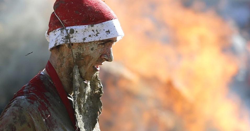 Competidor fantasiado de Papai Noel fica todo sujo de lama durante uma proiva de cross country na Áustria
